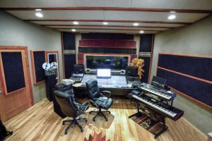 Wide angle shot of a modern high tech recording studio that includes various methods of recording, digital and analog, a wooden floor, sound console, board or desk, computer workstation, electronic keyboards and a window into an isolation booth.